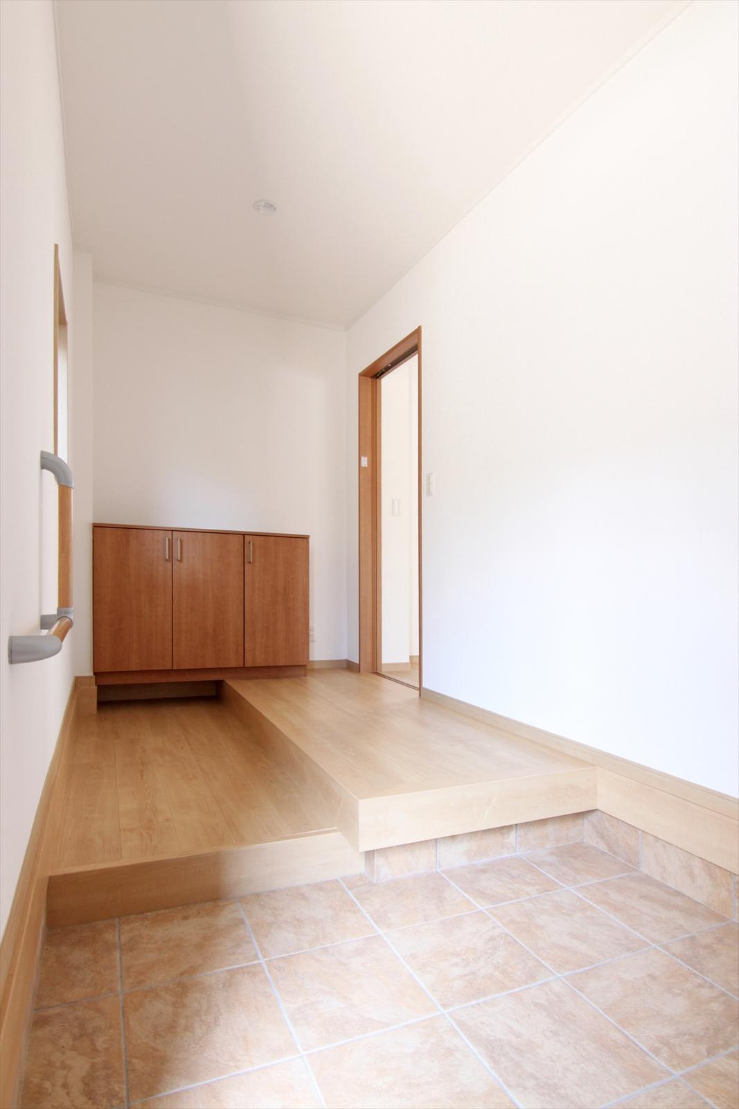 玄関ドアは引戸に、土間スペースも広く取りホールに上がる部分には手すりを付けて安全な出入りをサポートします。